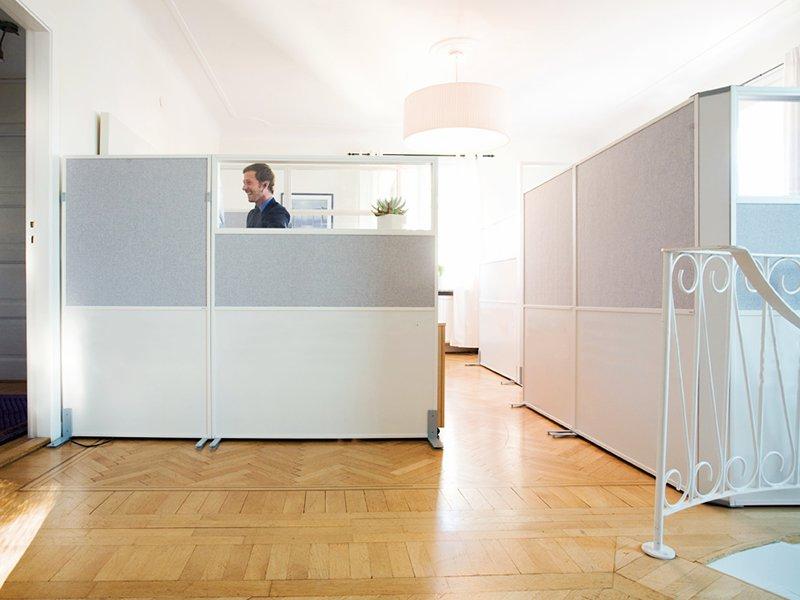 Ljuddämpande skärmväggar i ljust grått, vitt och glas förbättrar ljudmiljön på kontoret